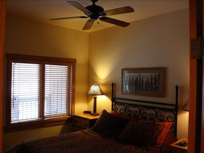 Guest Room with Queen sized bed, ceiling fan and flat screen TV.