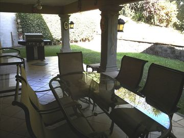 Outdoor patio with seating and gas grill.