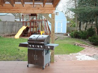 Kent house photo - BBQ, looking out to backyard with playset, & fire pit