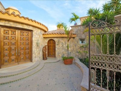 Elegant Courtyard Entryway with large hand carved doors and gated entry