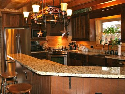 Gourmet kitchen featuring granite counters and stainless steel appliance.