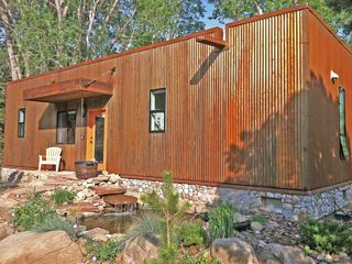 Taos house rental - Taos Rio Eco Dwelling, weathering steel and stone exterior, pond with waterfall