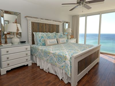 King bed with distressed headboard, designer bedding, floor to ceiling windows!