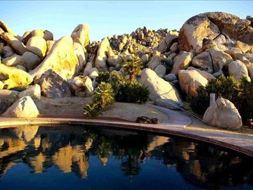 Joshua Tree house rental - Salt water pool surrounded by boulders. Beyond ridge is the Joshua Tree Park.