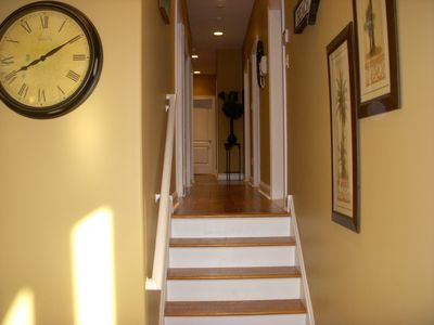 Stairs leading to 2nd level & hallway to 5 bedrooms, 3 bathrooms, & laundry room