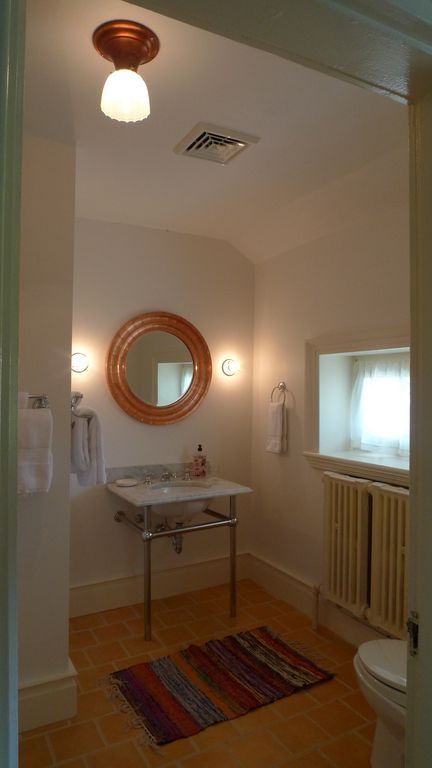 Copper mirror and marble sink in tiled full bath