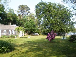 Dennis Village house photo - Lawn of property with boathouse at the right by the lake.