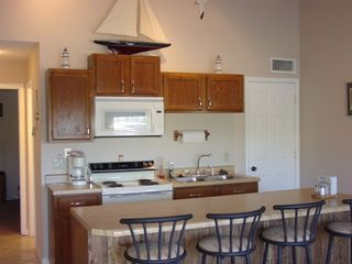 Kitchen with Refrigerator, Dishwasher, Stove, Microwave, Pots and Pans.
