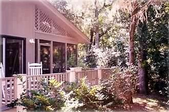 Our tranquil back deck with Adirondack chairs, surrounded by Live Oaks