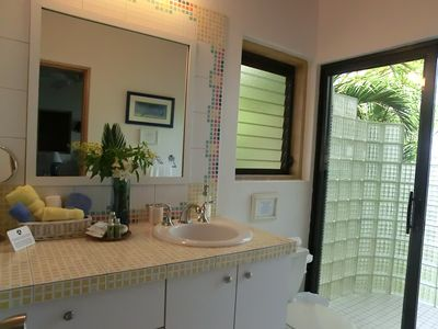 Caribe #1 Suite's en suite bathroom and glass and tile shower with ocean view.