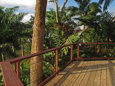 Downstairs deck with tropical landscaping on the side of the house