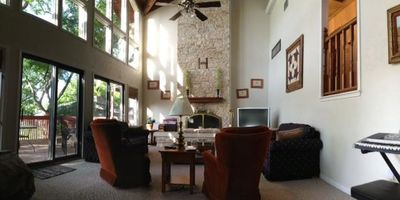Panoramic shot of living room, showing windows with view of Lake Austin.