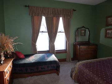 Bedroom with one queen and one twin sized bed, has its own half bath.