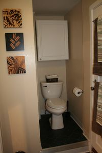 Commode tucked away in the corner of the bathroom.