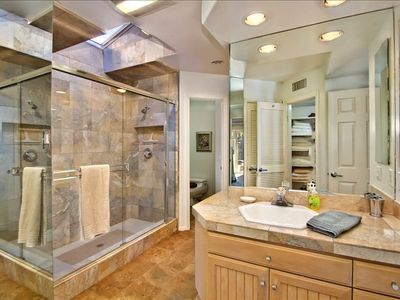Master bathroom with jetted bathtub, separate shower, and his and hers sinks.
