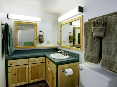 Mid-bath remodel with corner vanity, convenience shelf, & indiglo nite light.
