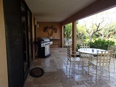 Lanai with two tables with eight chairs and BBQ.