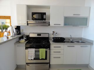 Juan Dolio apartment photo - Kitchen: Range, microwave, cooking utensils, water cooler & washing machine.