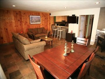 Mammoth Lakes condo rental - Cozy living room with views, tv, internet, wood stove, dining room table, patio