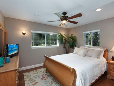 Luxurious guest bedroom with gorgeous views of landscaping.