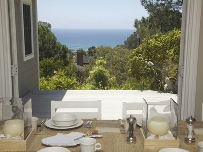 Dining table, open to deck with views to ocean and pool.