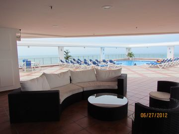 Rooftop Social Area with bar, sink, grille, tables and beautiful Pool and views.