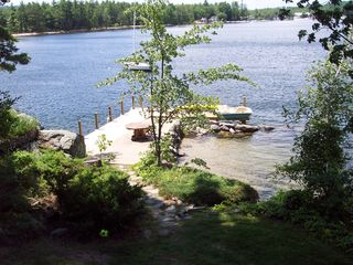Gilford house photo - dock space for 30 foot boat and day guest. Sandy beach. Clear water swimming.