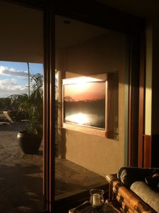 "80"" HD outdoor TV witin custom wood case. Picture on TV is a sunset reflection."
