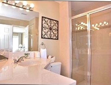 Master bath includes tiled shower with bench, luxury linens, and plenty of space
