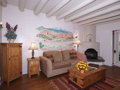 Sitting room with kiva fireplace, wood floors, ceiling vigas, hand painted mural