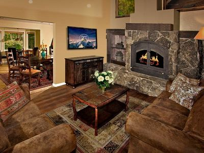 Living room with stone fireplace and vaulted ceilings