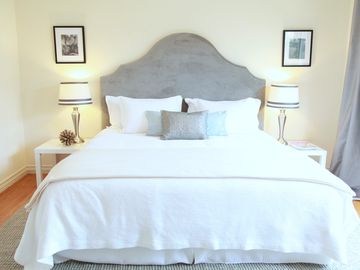 Comfortable king-sized bed with soft white sheets.