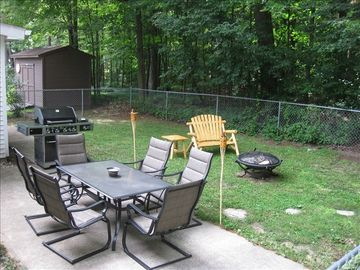Fenced in backyard with patio, fire pit, and large grill.