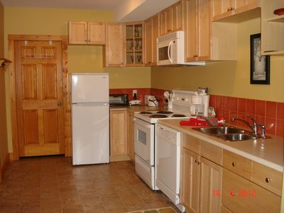 Laundry room is through the door at the end of the kitchen, beside the fridge.