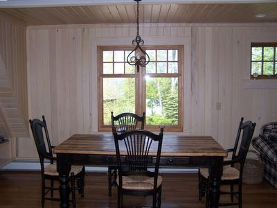 Dining table with view of lake--basswood paneling and cherry wood floors.