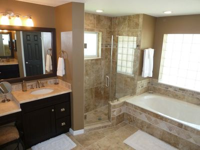 Master Bathroom showing ladies side vanity, walk in shower and large garden tub