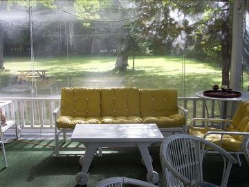 Lakefront porch, view of side yard, with rain shades drawn.