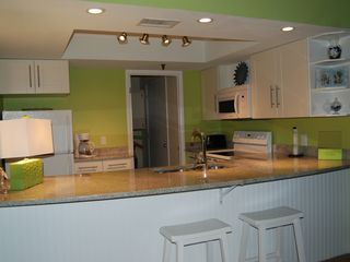 Redington Shores condo photo - The bright kitchen has plenty of counter space, bar stools and great Gulf views.