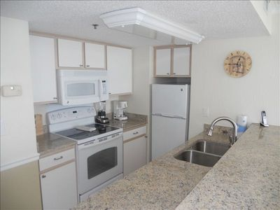 Kitchen featuring granite countertops, new appliances and cookware