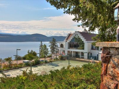 Lake Okanagan Resort Chalet with the  lighted tennis courts in the fore ground.