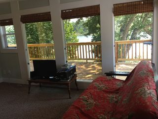 Sunroom lake view with 2 full-size futons, hamper, & luggage rack (no closet).