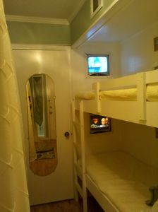 Another view of bunk beds with built-in TVs looking down the hall