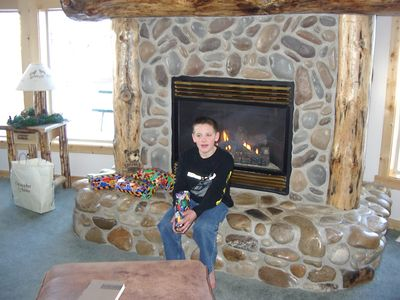 grandson in front of rock fireplace