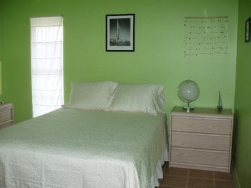 """The Green Room"" with queen size bed and large closet."