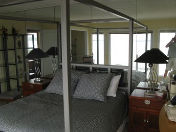 Master bedroom looks out on the sunroom and the ocean beyond