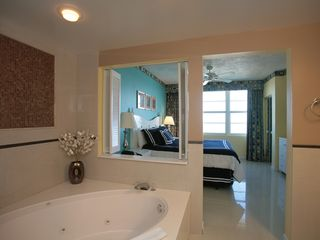 View from master suite bath towards king size bed and ocean front window. - Daytona Beach condo vacation rental photo