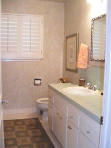 Hall way bathroom with stand up shower.