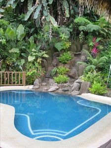 Sparkling tiled swimming pool features a rock waterfall in a lush setting.