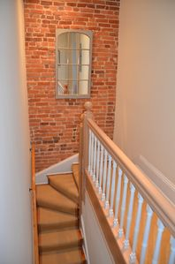 Original staircase to second level with lovely exposed brick wall