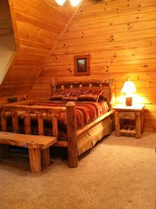 Upstairs bedroom has comfy queen log bed and TV